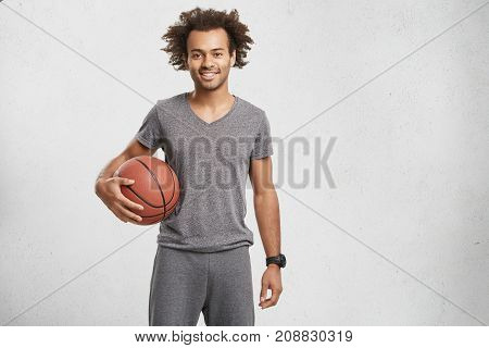 Horizontal Portrait Of Basketball Player Dressed Casually, Holds Ball, Being Glad After Successful G