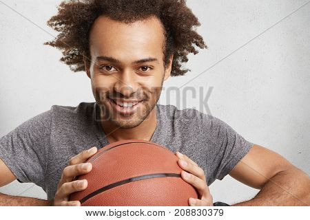 Happy Delightful Male Prepares For Serious Basketball Competition, Holds Ball, Waits For Team. Dark