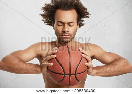 African American Male Closes Eyes, Tries To Concentrate As Holds Basket Ball, Prepares For Serious R