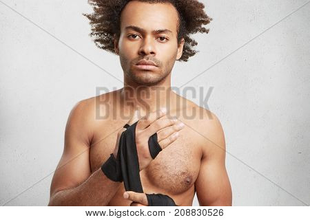 Strong Mixed Race African American Man Wrapes Hands With Bandage Tape, Gets Prepared For Fighting. Y
