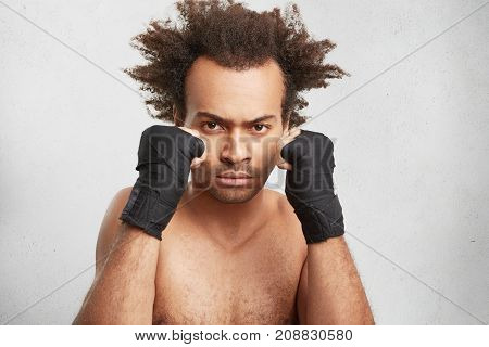 I Need Only Victory. Confident Fighter With Serious Expression And Taped Hands Look Angrily At Oppon