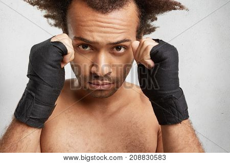 Close Up Portrait Of Successful Male Boxer Shows Strong Arms And Clenched Fists Wrapped By Protectiv
