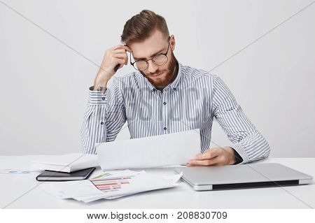 Serious Concentrated Bearded Man Dressed Formally, Reads Document Or Contract, Sits At Work Place, T