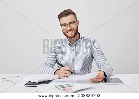 Busy Smiling Bearded Male Enterpreneur Holds Pen And Document, Has Pleased Expression As Signs Succe