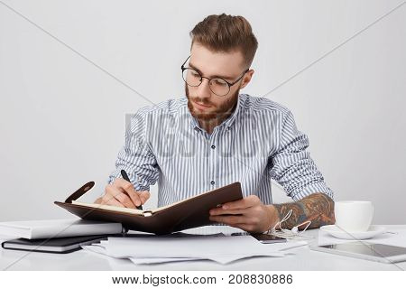 Working Moments. Concentrated Serious Stylish Tattooed Man Wears Formal Shirt And Round Glasses, Sit