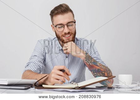 Portrait Of Stylish Hipster Guy With Colored Tattoo On Hand, Writes Notes In Notebook, Drinks Coffee