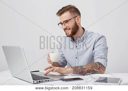Indoor Shot Of Creative Business Worker With Tattooed Arms, Has Thick Beard, Holds Mug Of Tea, Looks