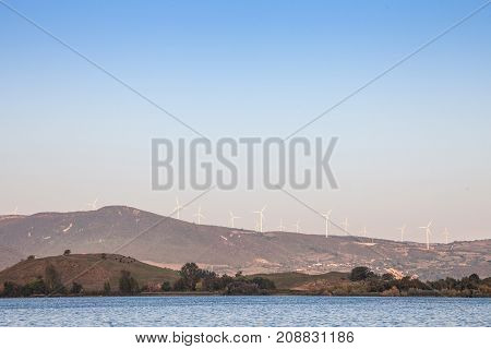 Romanian Wind Farm with Wind Turbines and windmills facing the Danube river in the Iron Gates valley. Due to the heavy winds in the gorges it has been chosen as a spot to develop green energies