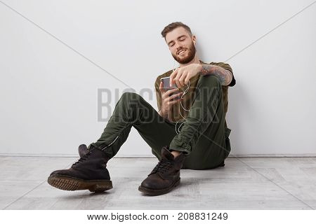 Restful Bearded Fashionable Guy Enjoys Favourite Music As Uses Smart Phone And Earphones, Wears Styl