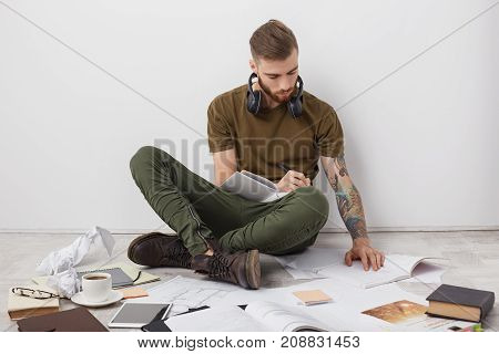 Indoor Shot Of Hipster Male With Trendy Hairstyle, Thick Berad And Tattooed Arms, Looks Attentively