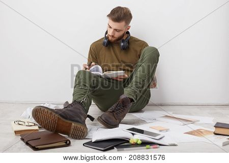 Busy Male Student Wears Casual Clothes And Boots, Writes Notes, Being Invlolved In Studying Before S