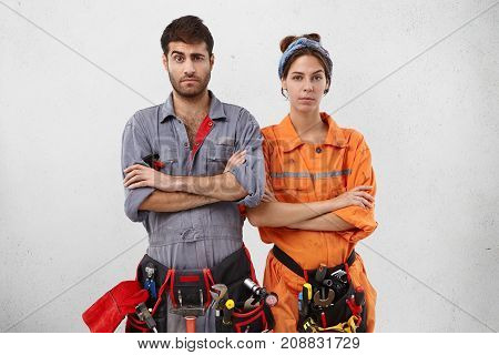Two Maintenance Workers Stand Next To Each Other, Keep Hands Folded, Raise Eyebrows In Bewilderment,