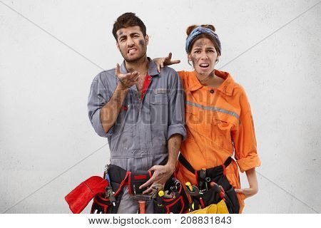 Sad Dissatisfied Male Car Mechnic And His Pretty Wife Who Helps Husband To Repair Automobiles, Have