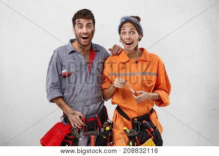 Emotional Happy Female And Male Carpenters Look With Excitement Or Surprisment, Hold Necessary Equip