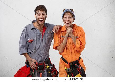 Indoor Picture Of Emotional Female And Male Plumbers Being Excited As Promoted At Work, Recieve Awar