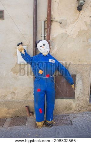 Scarecrow dressed as a mechanic leaning on a wall in Castiglione del Lago