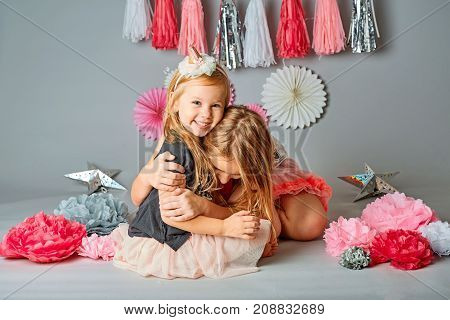 Two cute young sisters posing together in a studio. Vertically framed shot isolated against a gray studio background. The older sister is hugging the younger one. Both are smiling at the camera