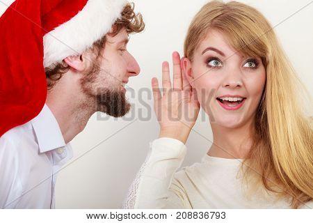 Man In Santa Hat Whispering To Woman Ear.