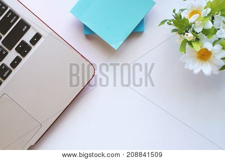Top view of workspace computer laptop notepad flower decoration on white table with copyspace