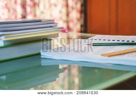 Tutorial document sheet and book for an examination with blurred Thai text on the table in the living room
