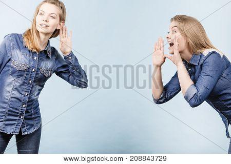 Two women talking gossip telling tales girls talk having fun wearing jeans outfit.