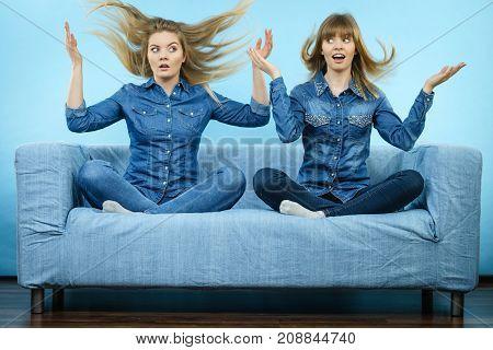 Two shocked women wearing jeans shirts having windblown blonde hair. Blue background.