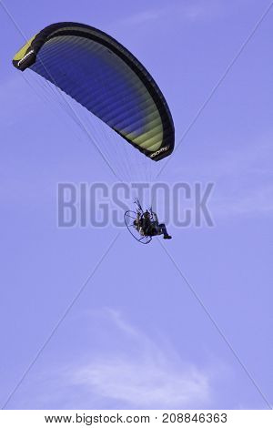 Saint Quentin, New Brunswick - August 17, 2011 - Vertical of a man sitting on a motorized aerial fan seat attached to a para-sail flying through the blue sky background in, near Bathurst, NB on a bright sunny day with blue skies and clouds in August.
