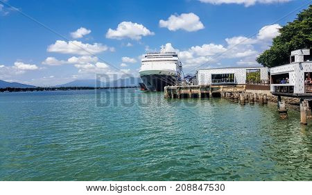a beautiful day in Cairns Australia with view of esplanade and ship docked in harbor