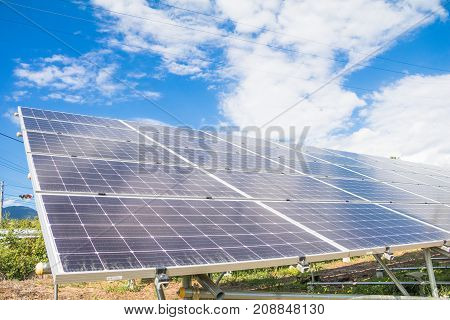 Solar power panels for innovation green energy for life with mountains and blue sky background.