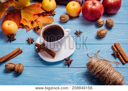 Black coffee in a white cup with a saucer with cinnamon and badon on a wooden blue surface among ripe apples of maple leaves and a hank with threads and walnuts