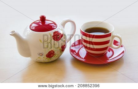 Striped Cup With Tea On A Saucer And Brewer With A Poppy Picture On A Wooden Table Top