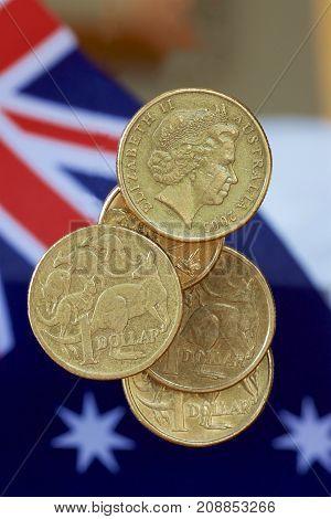 Australian dollar coins on a background of the Australian flag.