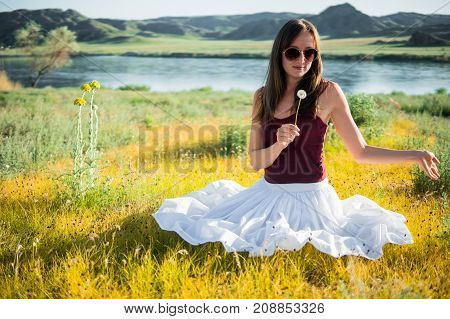 Woman Like A Fairy On The Magic Field Near The River. Young Woman With Dandelion. Fantasy Style