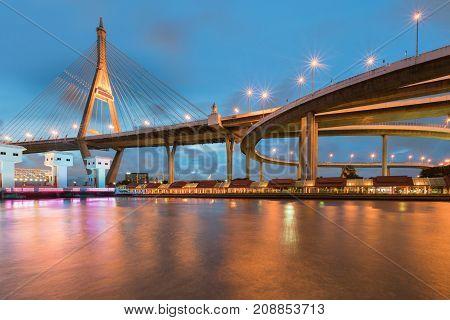 Night twilight suspension bridge over white watergate
