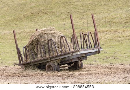 agricultural outdoor scenery with hay and hayrack at a meadow
