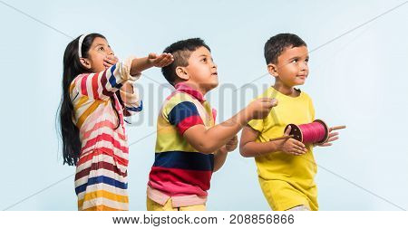 Kite or Patang flying in India, three cute little indian kids enjoying Kite flying in Makar sankranti festival, standing with chakri or wooden spindal and holding thread in excitement on blue background