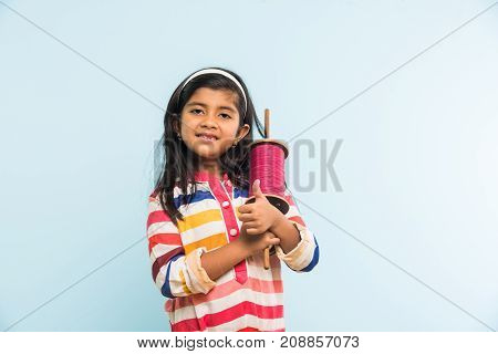 Kite or Patang flying in India, cute and happy little indian  girl  holding chakri or wooden spindal and standing over blue background on Makar Sankranti Festival