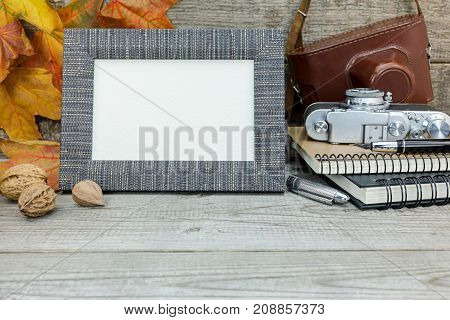 Classic Camera, Notebooks, Fountain Pen, Empty Photo Frame On Wooden Desk With Dried Vibrant Leaves