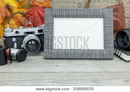 Grey Wooden Background With Classic Camera, Empty Photo Frame, Lens And Film Rolls