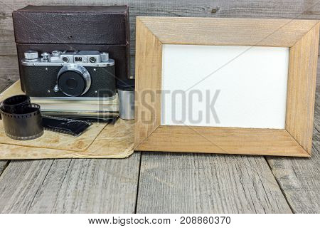 Retro Camera, Negative Films, Old Photos And Empty Frame On Grey Wooden Table