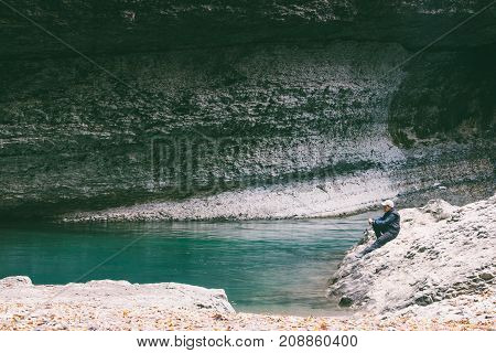 boy teenager sits on a stone beach blue of a green mountain river