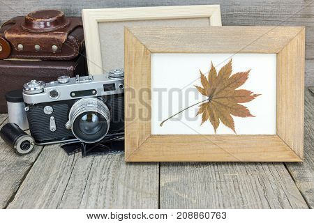 Empty Photo Frame And Vintage Camera With Leather Case On Grey Wooden Table