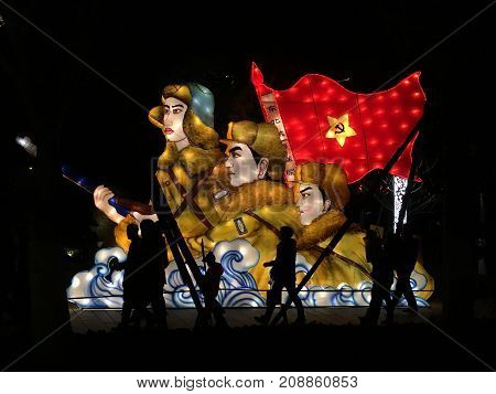 Wuhan China, 10 February 2017: Chinese people walking in front of an illuminated communism sign lantern with red flag and soldiers during night at Wuhan lantern festival