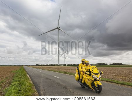 Le Gault-Saint-Denis France - October 08 2017: The iconic yellow LCL bike driving on a road in the plain with windmills in a cloudy day during the Paris-Tours road-cycling race.