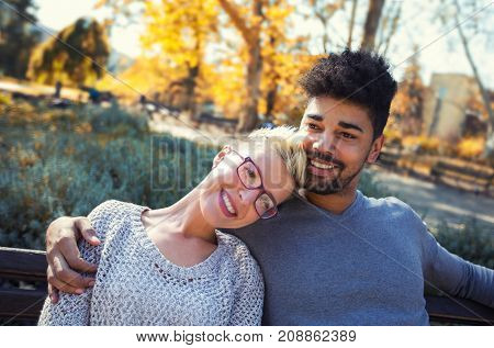Outdoor portrait of romantic and happy mixed race young couple in park