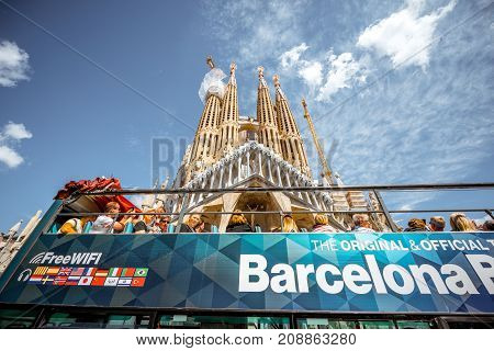 BARCELONA, SPAIN - August 16, 2017: View on the famous unfinished Roman Catholic church Sagrada Familia with tourist bus in Barcelona, designed by Catalan architect Antoni Gaudi