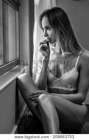 Beautiful Blonde Woman In White Lingerie Posing Near A Window.
