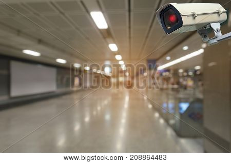 CCTV security camera system operating with blurred view of subway train station surveillance security and safety technology concept
