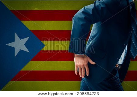 Catalonia separatism concept. Businessman (financier, bank employee, CEO, manager) run away (escape) from Catalonia represented by flag.