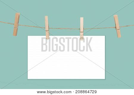 Rope with empty white paper frames with space for copy and clothespins on a blue background